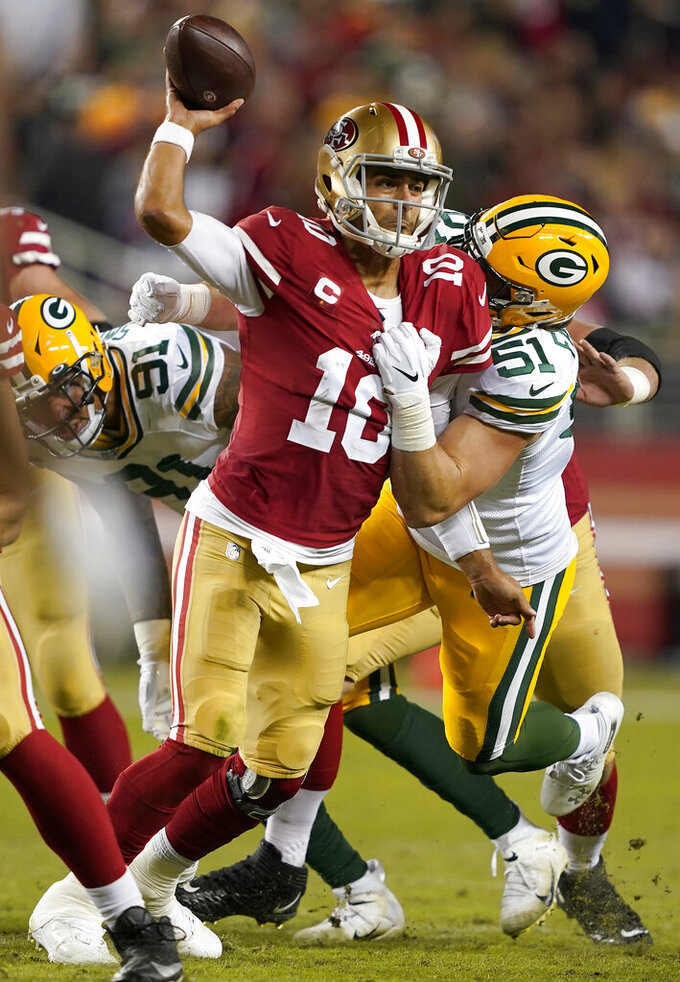 San Francisco 49ers quarterback Jimmy Garoppolo (10) passes the ball as he is pressured by Green Bay Packers linebacker Kyler Fackrell (51) during the first half of an NFL football game in Santa Clara, Calif., Sunday, Nov. 24, 2019. (AP Photo/Tony Avelar)