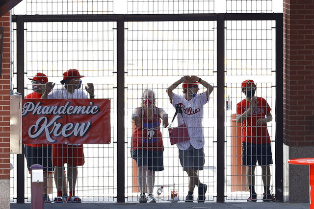 FILE - In this Aug. 5, 2020, file photo, Philadelphia Phillies fans watch from an outfield gate during the first inning of the first baseball game in doubleheader against the New York Yankees, in Philadelphia. The Phandemic Krew are the Phillies biggest fans.(AP Photo/Matt Slocum, File)
