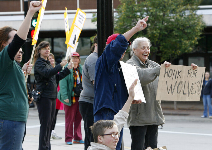 FILE - In this Oct. 15, 2013, file photo, Ann Emerson, of Madison, far right, holds a sign during a wolf hunt protest outside the Capitol in Madison, Wis. A coalition of animal rights groups planned to file a lawsuit Tuesday, Aug. 31, 2021, to stop Wisconsin's fall wolf hunt. (Michelle Stocker/The Capital Times via AP, File)