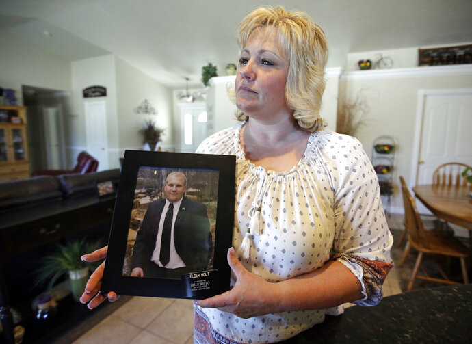 FILE - In this July 13, 2016, file photo, Laurie Holt holds a photograph of her son Joshua Holt, who has been jailed in Venezuela for several months, at her home, in Riverton, Utah. In two short videos shot on a cell phone and posted Wednesday, May 16, 2018, on his Facebook page Joshua Holt said his life was threatened during a disturbance by inmates that include President Nicolas Maduro's top opponents. Venezuela's chief prosecutor sent a commission to the jail to discuss the prisoners' demands. (AP Photo/Rick Bowmer, File)