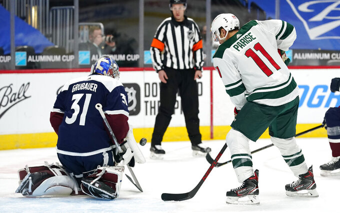 Colorado Avalanche goaltender Philipp Grubauer, left, stops a redirected shot off the stick of Minnesota Wild left wing Zach Parise in the second period of an NHL hockey game Tuesday, Feb. 2, 2021, in Denver. (AP Photo/David Zalubowski)