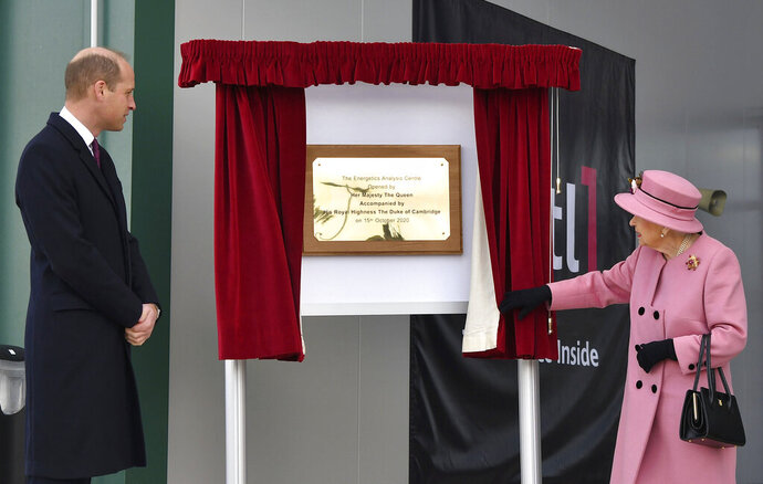 Britain's Prince William looks on as Queen Elizabeth II unveils a plaque to officially open the new Energetics Analysis Centre at the Defence Science and Technology Laboratory (DSTL) at Porton Down, England, Thursday Oct. 15, 2020, to view the Energetics Enclosure and display of weaponry and tactics used in counter intelligence. (Ben Stansall/Pool via AP)