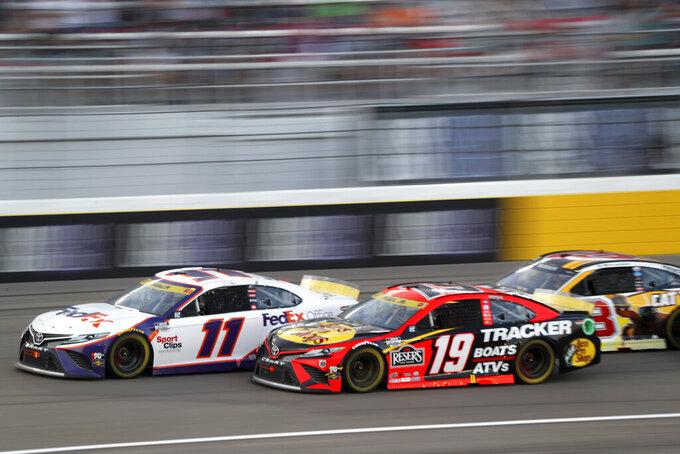 NASCAR Cup Series driver Denny Hamlin (11) leads Martin Truex Jr. (19) and Tyler Reddick (8) down a straightaway during a NASCAR Cup Series auto race at the Las Vegas Motor Speedway, Sunday, Sept. 26, 2021, in Las Vegas. Hamlin won the race. (AP Photo/Steve Marcus)