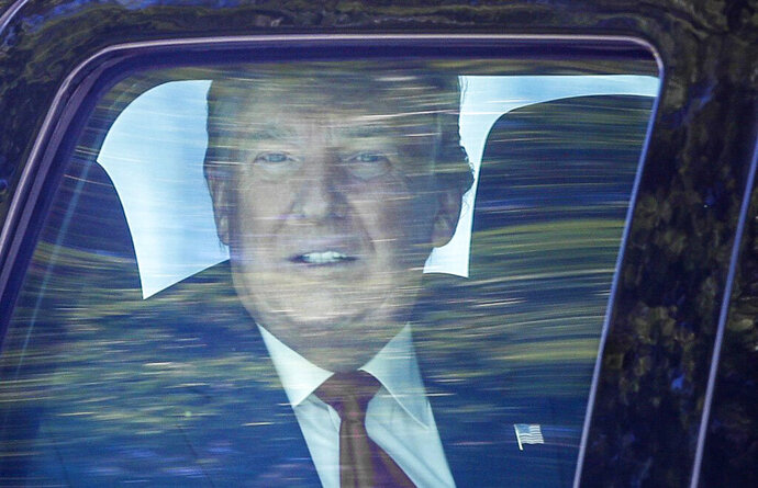 Former President Donald Trump looks out his window as his motorcade drives through West Palm Beach, Fla., on his way to his Mar-a-Lago club in Palm Beach after arriving from Washington aboard Air Force One on Wednesday, Jan. 20, 2021. (Damon Higgins/The Palm Beach Post via AP)