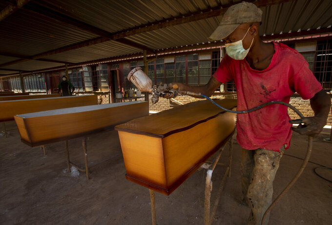 A worker finishes the details on a production line of coffins in his workshop, in Evaton, south of Johannesburg, South Africa, Monday, Feb. 15, 2021.  Maseko, says the material and cost for making coffins has gone up due to less suppliers due the impact of Covid-19 on most businesses. (AP Photo/Themba Hadebe)