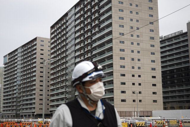 FILE - In this March 23, 2020, file photo, a worker walks through the athletes village for the Tokyo 2020 Olympics, in Tokyo. Tokyo's governor is considering the possibility of using the unfinished Olympic Athletes Village as a temporary hospital for coronavirus infected patients. The massive village on Tokyo Bay could house up to 18,000 people during the Olympics. (AP Photo/Jae C. Hong, File)