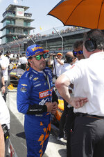 FILE - In this May 18, 2019, file photo, Fernando Alonso, of Spain, talks with his crew as he prepares to qualify for the Indianapolis 500 IndyCar auto race at Indianapolis Motor Speedway in Indianapolis. Alonso will once again attempt to complete motorsports' version of the Triple Crown with a return to the Indianapolis 500 in May with McLaren. (AP Photo/Michael Conroy, File)