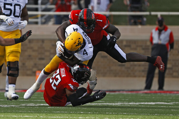 Texas Tech's Ja'Marcus Ingram (22) and Krishon Merriweather (1) tackle West Virginia's Leddie Brown (4) during the first half of an NCAA football game on Saturday, Oct. 24, 2020, in Lubbock, Texas. (AP Photo/Brad Tollefson)