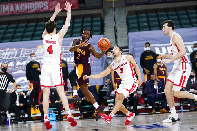 Iona's Asante Gist (2) passes the ball against Fairfield's Jake Wojcik (4), Caleb Green (0) and Zach Crisler (20) in the second half of an NCAA college basketball game during the finals of the Metro Atlantic Athletic Conference tournament, Saturday, March 13, 2021, in Atlantic City, N.J. (AP Photo/Matt Slocum)