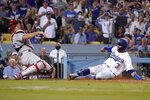 Los Angeles Dodgers' Chris Taylor, right, scores on a single by Zach McKinstry as Philadelphia Phillies catcher J.T. Realmuto misses the ball during the fourth inning of a baseball game Tuesday, June 15, 2021, in Los Angeles. (AP Photo/Mark J. Terrill)