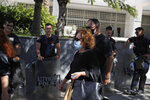 Magda Fyssa, center, the mother of late Greek rap singer Pavlos Fyssas, who was stabbed and killed by a supporter of the extreme right Golden Dawn party in 2013 triggering a crackdown on the party, walks into the court for the sentencing announcement of the Golden Dawn trial, in Athens, Wednesday, Oct. 14, 2020. The lengthy sentencing procedure is the final chapter in a more than five-year politically charged trial that encompassed four cases and involved 68 defendants, more than 200 witnesses and over 60 lawyers.(AP Photo/Thanassis Stavrakis)
