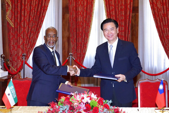 In this photo released by the Taiwan Ministry of Foreign Affairs, Taiwan's Foreign Minister Joseph Wu, right, and his counterpart from Somaliland, Yasin Hagi Mohamoud shake hands after signing an agreement for setting up representative offices in their respective territories in Taipei on Feb. 26, 2020. Taiwan has scored a rare diplomatic victory in establishing relations with the independent region of Somaliland, according to a July 1, 2020 post on the on the Taiwanese foreign ministry's website. (Taiwan Ministry of Foreign Affairs via AP)