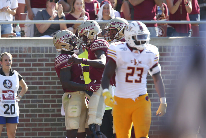 Florida State's Cam Akers, center left, celebrates scoring a touchdown with James Blackman against Louisiana-Monroe in the first quarter of an NCAA college football game, Saturday, Sept. 7, 2019 in Tallahassee Fla. (AP Photo/Steve Cannon)