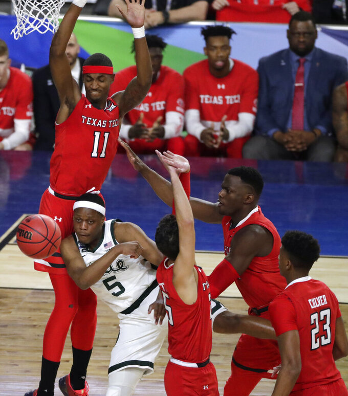 Michigan State guard Cassius Winston (5) passes the ball in front of Texas Tech forward Tariq Owens (11) during the first half in the semifinals of the Final Four NCAA college basketball tournament, Saturday, April 6, 2019, in Minneapolis. (AP Photo/Matt York)