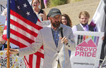FILE - In this June 14, 2018 file photo, Utah County Commissioner Nathan Ivie speaks as he holds the American flag during a news conference  in Provo, Utah. Ivie, a Republican lawmaker in an area of Utah where many residents are member of The Church of Jesus Christ of Latter-day Saints, has publicly come out as gay. Ivie said Wednesday, May 22, 2019, his announcement was inspired in part by his work with families who have lost gay children to suicide. (AP Photo/Rick Bowmer)