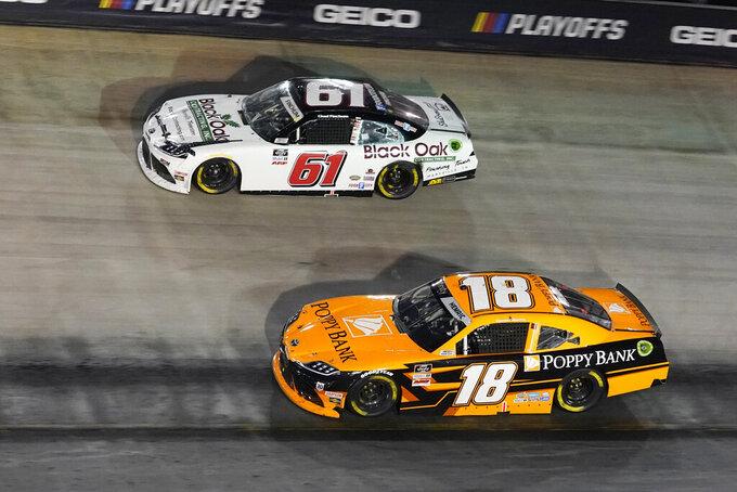 Chad Finchum (61) and Daniel Hemric (18) drive through a turn during a NASCAR Xfinity Series auto race at Bristol Motor Speedway Friday, Sept. 17, 2021, in Bristol, Tenn. (AP Photo/Mark Humphrey)