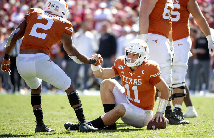 Texas quarterback Sam Ehlinger (11) is helped up by running back Roschon Johnson (2) after being sacked in the second half of an NCAA college football game against Oklahoma at the Cotton Bowl, Saturday, Oct. 12, 2019, in Dallas. Ehlinger was sacked 9 times as Oklahoma won 34-27. (AP Photo/Jeffrey McWhorter)
