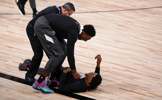 Miami Heat's Bam Adebayo, left, and Miami Heat's Udonis Haslem, right, horseplay before the first half in Game 3 of basketball's NBA Finals, Sunday, Oct. 4, 2020, in Lake Buena Vista, Fla. (AP Photo/Mark J. Terrill)