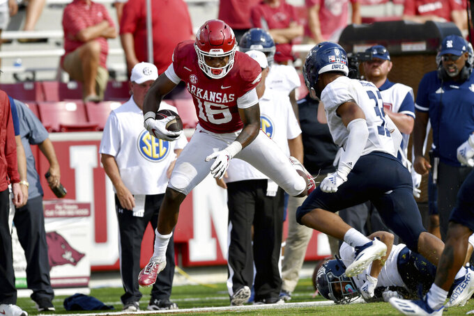 Arkansas receiver Treylon Burks (16) is knocked out of bounds by Rice defenders after making a catch during the second half of an NCAA college football game Saturday, Sept. 4, 2021, in Fayetteville, Ark. (AP Photo/Michael Woods)