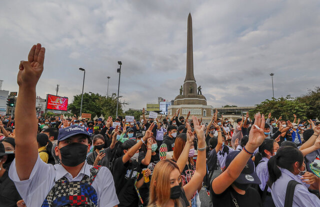 Pro-democracy activists flash three-fingered salute during a demonstration at Victory Monument in Bangkok, Thailand, Wednesday, Oct. 21, 2020. Student activists applied to a Bangkok court Wednesday to revoke a state of emergency the government declared last week to try to rein in Thailand's growing protests. Demonstrations have continued daily in a movement that calls for Prime Minister Prayuth Chan-ocha to step down, for a more democratic constitution and for reforms to the monarchy — a revered institution traditionally treated as sacrosanct in Thailand. (AP Photo/Sakchai Lalit)