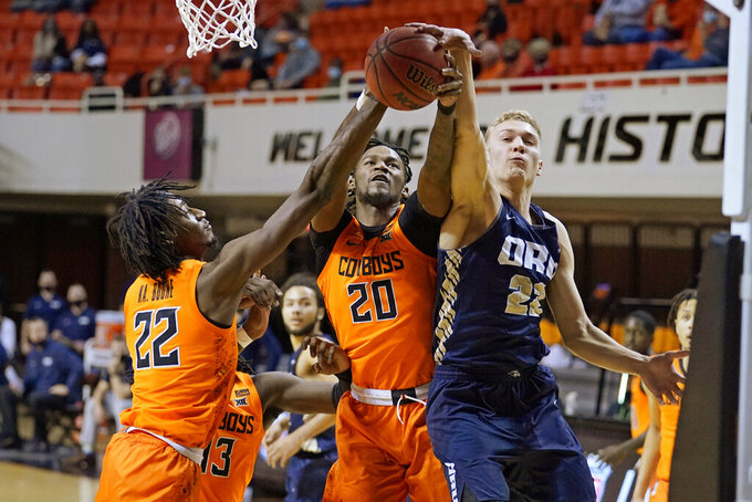 Oklahoma State forward Kalib Boone, left, and guard Keylan Boone (20) and Oral Roberts forward Francis Lacis, right, reach for a rebound during the first half of an NCAA college basketball game Tuesday, Dec. 8, 2020, in Stillwater, Okla. (AP Photo/Sue Ogrocki)