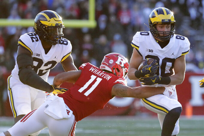 Michigan wide receiver Oliver Martin, right, runs with the ball as Rutgers defensive back Isaiah Wharton (11) wraps him up for the tackle during the first half of an NCAA college football game, Saturday, Nov. 10, 2018, in Piscataway, N.J. Michigan's Nick Eubanks, left, tries to block on the play. (AP Photo/Julio Cortez)