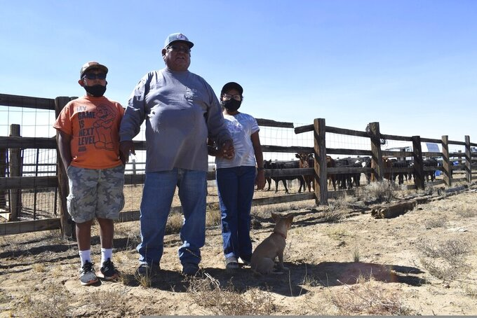 In this Oct 1, 2020 image, Navajo rancher Timothy Largo and his grandchildren pose for a photograph outside a corral at the Sims Ranch near Crownpoint, New Mexico. Navajo ranchers impacted by the pandemic and ongoing drought may soon qualify for assistance to supplement their livestock with hay and grain. (Vida Volkert/Gallup Independent via AP)
