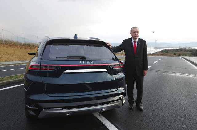 Turkish President Recep Tayyip Erdogan poses with a prototype of a domestically produced electric car, in Gebze, Turkey, Friday, Dec. 27, 2019. Turkey's president has unveiled prototypes of what he hopes will be the country's first domestically produced car. In a ceremony on Friday, Recep Tayyip Erdogan showcased the SUV and sedan models of the electric automobile, known for now as TOGG after the Turkish consortium that plans to produce the vehicles. (Presidential Press Service via AP, Pool)