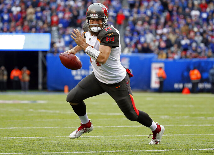 FILE - In this Nov. 18, 2018, file photo, Tampa Bay Buccaneers quarterback Ryan Fitzpatrick (14) rushes for a touchdown against the New York Giants during an NFL football game in East Rutherford, N.J. Fitzpatrick has agreed to terms on a two-year contract with the Miami Dolphins, who were in the market for a replacement to Ryan Tannehill. Fitzpatrick, 36, has a 50-75-1 record as a starter for seven NFL teams. He started seven games for Tampa Bay last year and had a passer rating of 100.4, which ranked ninth in the league. (AP Photo/Adam Hunger, File)