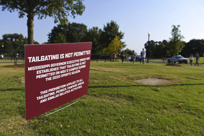 Fans walk past a sign that says tailgating is prohibited in the Junction tailgate area before an NCAA college football game between Mississippi State and Arkansas in Starkville, Miss., Saturday, Oct. 3, 2020. (AP Photo/Thomas Graning)