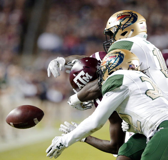 Texas A&M wide receiver Quartney Davis, left, can't make the reception as UAB safety Broderick Thomas (22) and cornerback Dy'jonn Turner, right, defend during the first half of an NCAA college football game Saturday, Nov. 17, 2018, in College Station, Texas. UAB was called for interference. (AP Photo/Michael Wyke)