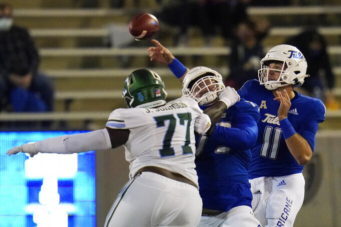Tulsa quarterback Zach Smith (11) throws user pressure from Tulane nose tackle Jeffery Johnson (77) as offensive lineman Dylan Couch blocks during the first half of an NCAA college football game in Tulsa, Okla., Thursday, Nov. 19, 2020. (AP Photo/Sue Ogrocki)