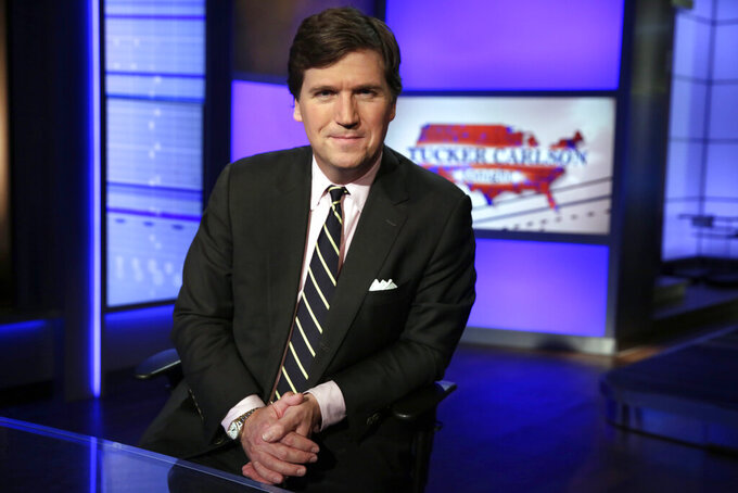 "FILE - In this Thursday, March 2, 2107 file photo, Tucker Carlson, host of ""Tucker Carlson Tonight,"" poses for a photo in a Fox News Channel studio in New York. The Anti-Defamation League has called for Fox News to fire prime-time opinion host Tucker Carlson because he defended a white-supremacist theory that says whites are being ""replaced"" by people of color. In a letter to Fox News CEO Suzanne Scott on Friday, April 9, 2021the head of the ADL, Jonathan Greenblatt, said Carlson's ""rhetoric was not just a dog whistle to racists — it was a bullhorn.""  (AP Photo/Richard Drew, File)"