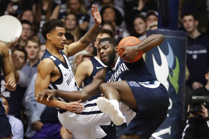 Villanova forward Eric Paschall (4) and Butler forward Jordan Tucker (1) get tied up as they go for a rebound in the first half of an NCAA college basketball game in Indianapolis, Tuesday, Jan. 22, 2019. (AP Photo/Michael Conroy)