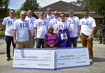 """Jessie Hamilton, seated, is surrounded by LSU FIJI graduates as they gathered to surprise their former house kitchen staff member, Saturday, April 3, 2021, and celebrate """"Jessie Hamilton Day"""" in Baker, La. (Hilary Scheinuk/The Advocate via AP)"""