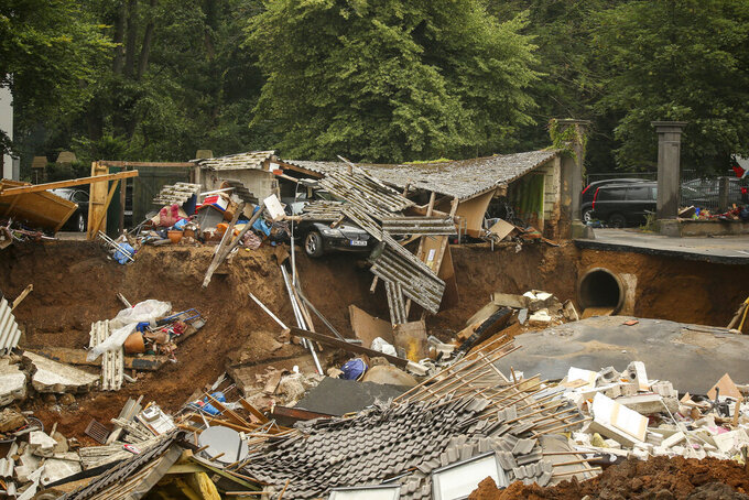 """FILE - In this Friday, July 16, 2021 file photo, debris is strewn in the Blessem district of Erftstadt, Germany, after heavy rains caused mudslides and flooding in the western part of Germany. On Friday, July 23, 2021, The Associated Press reported on stories circulating online incorrectly asserting a manipulated photo shows a BMW car caught in floodwaters with anti-Greta Thunberg sticker on its rear window. But photojournalist David Young, who captured the original, unaltered photo for the German media outlet Bild in the city of Wuppertal, says, """"It is my photo and it has been manipulated. … The sticker is fake."""" (David Young/dpa via AP, File)"""