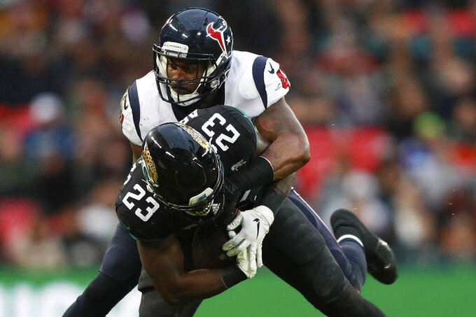 Houston Texans inside linebacker Zach Cunningham (41) tackles Jacksonville Jaguars running back Ryquell Armstead (23) during the second half of an NFL football game at Wembley Stadium, Sunday, Nov. 3, 2019, in London. (AP Photo/Ian Walton)