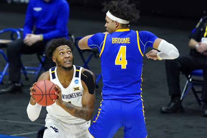 Morehead State's Johni Broome (4) tries to block the path of West Virginia's Derek Culver during the first half of a college basketball game in the first round of the NCAA tournament at Lucas Oil Stadium Friday, March 19, 2021, in Indianapolis. (AP Photo/Mark Humphrey)