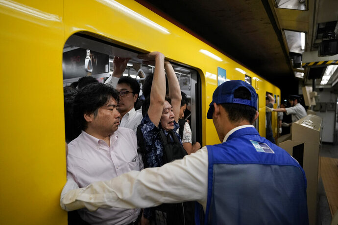 In this July 30, 2019, photo, a station attendant watches as a commuter struggles to squeeze himself into an overcrowded train during morning rush hours at Akasaka Mitsuke Station in Tokyo. Tokyo has one of the most advanced public transport systems in the world, but with less than one year to go before the city hosts the 2020 Olympic Games, local governments, companies and commuters are bracing for unprecedented strain the events could put on rail transit and highways. (AP Photo/Jae C. Hong)