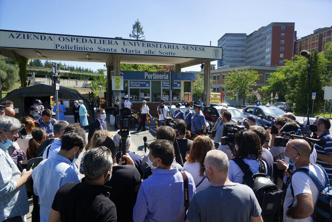 "Reporters gather outside the Santa Maria alle Scotte hospital as they wait for a medical bulletin on Alex Zanardi, in Siena, Italy, Saturday, June 20, 2020. Italian race car champion-turned-Paralympic gold medalist Alex Zanardi remains in serious condition a day after crashing his handbike into a truck and smashing his face. A medical bulletin from the Santa Maria alle Scotte hospital in Siena says that Zanardi is hooked up to an artificial ventilator and has ""stable"" blood flow while his neurological status ""remains serious."" Zanardi was transported by helicopter to the hospital after crashing near the Tuscan town of Pienza during a relay race Friday. (Alessandro La Rocca/LaPresse via AP)"