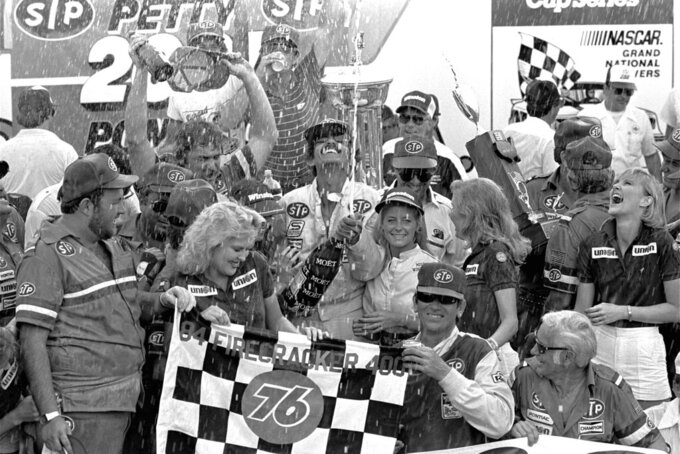 FILE - In this Wednesday, July 4, 1984, file photo, Firecracker 400 winner Richard Petty showers the crowd with champagne in Victory Lane at Daytona International Speedway in Daytona Beach, Fla. It's weeknight racing at Darlington as NASCAR's comeback from the coronavirus continues with its first Wednesday race in 36 years on May 20, 2020. (AP Photo/Jann Zlotkin, File)