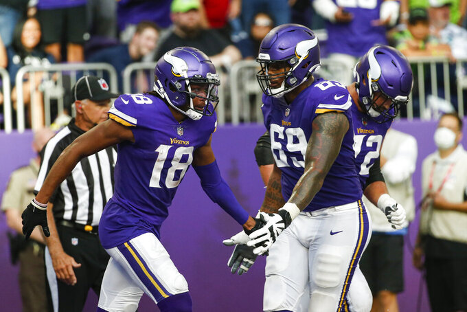Minnesota Vikings wide receiver Justin Jefferson (18) celebrates a touchdown with offensive tackle Rashod Hill (69) in the first half of an NFL football game against the Seattle Seahawks in Minneapolis, Sunday, Sept. 26, 2021. (AP Photo/Bruce Kluckhohn)