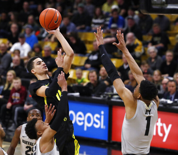 Oregon guard Will Richardson, left, goes up for a basket as Colorado guard Tyler Bey defend in the first half of an NCAA college basketball game Saturday, Feb. 2, 2019, in Boulder, Colo. (AP Photo/David Zalubowski)