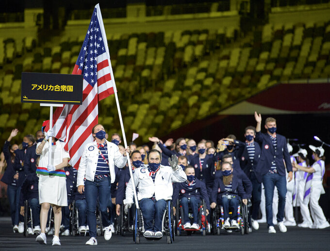 In this photo provided by the Olympic Information Service, United States Paralympic team athletes Melissa Stockwell and Charles Aoki  lead the team during the athletes parade at the opening ceremonies for the Tokyo 2020 Paralympic Games in Tokyo, Japan, Tuesday, Aug. 24, 2021.  (Joel Marklund for OIS via AP)