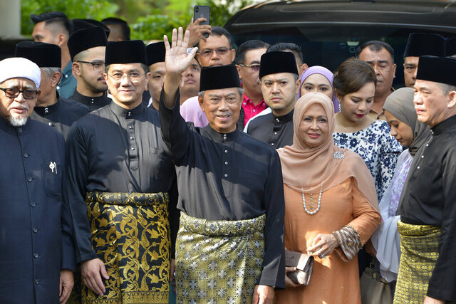 FILE - In this March 1, 2020, file photo, Muhyiddin Yassin, center, waves with his family and supporters as he prepares to leave his house for the palace to swear in as new prime minister, in Kuala Lumpur, Malaysia. Muhyiddin has postponed Parliament sitting by more than two months, effectively delaying plans by the former ruling alliance led by Mahathir Mohamad to seek a no-confidence vote against him. (AP Photo/Johnshen Lee, File)