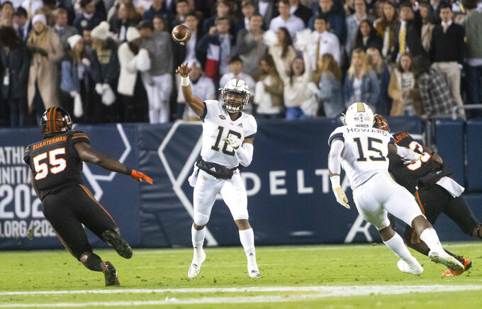 Georgia Tech quarterback TaQuon Marshall passes the ball with Miami linebacker Shaquille Quarterman (55) defending and running back Jerry Howard (15) trying to stop linebacker Zach McCloud (53) from reaching the quarterback during the first half of an NCAA college football game Saturday, Nov. 10, 2018, in Atlanta. (AP Photo/John Amis)