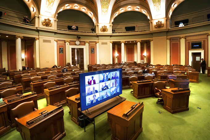 Legislatures are displayed on a monitor as they are sworn-remotely in groups of nine in the nearly-empty House Chamber at the Minnesota State Capitol, Tuesday, Jan. 5, 2021, in St. Paul, Minn. A few took the oath in person earlier. (Glen Stubbe/Star Tribune via AP)