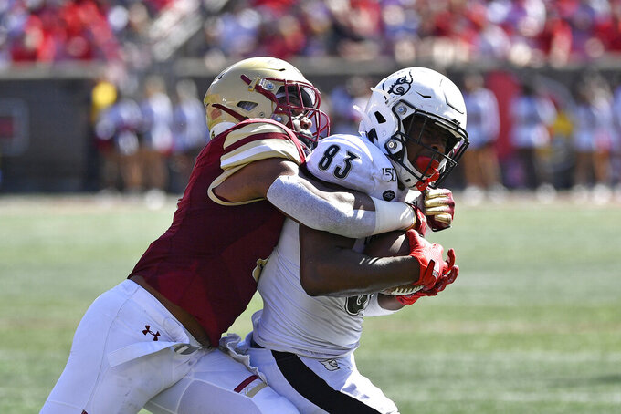 Louisville tight end Marshon Ford (83) is grabbed for behind by Boston College defensive back Jahmin Muse (8) during the second half of an NCAA college football game in Louisville, Ky., Saturday, Oct. 5, 2019. Louisville won 41-39. (AP Photo/Timothy D. Easley)