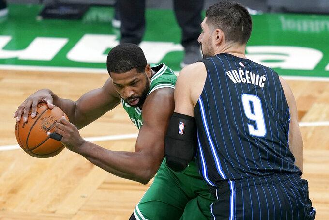 Boston Celtics forward Tristan Thompson, left, drives against Orlando Magic center Nikola Vucevic during the first half of an NBA basketball game Friday, Jan. 15, 2021, in Boston. (AP Photo/Elise Amendola)
