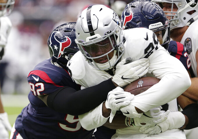 Oakland Raiders running back Josh Jacobs (28) is hit by Houston Texans nose tackle Brandon Dunn (92) on a run during the first half of an NFL football game Sunday, Oct. 27, 2019, in Houston. (AP Photo/Michael Wyke)